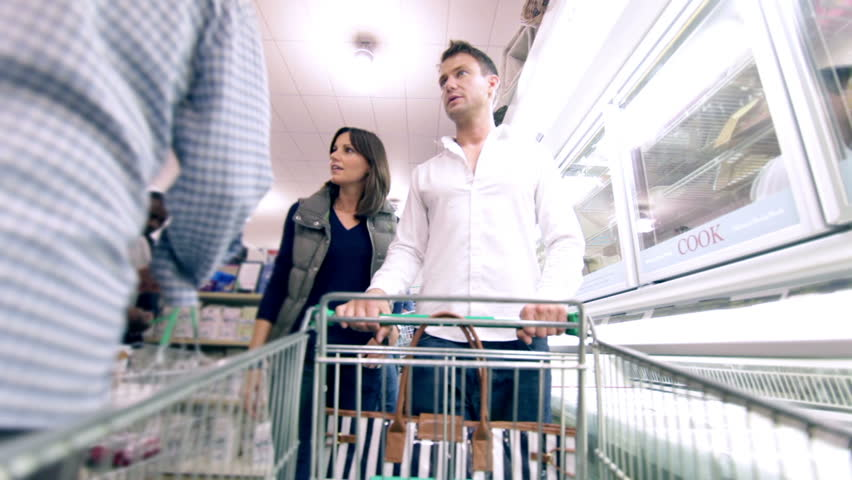 Customers shopping in a Supermarket and browsing products. Shopping trolley being filled with groceries and food.