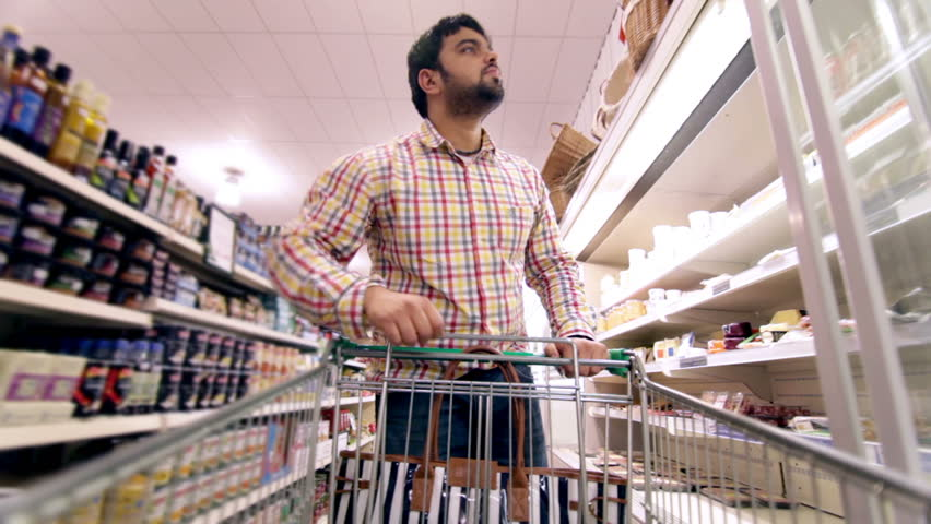 Customers Shopping In A Supermarket And Browsing Products ...