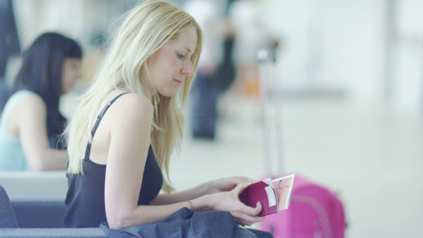 Young blonde woman sitting and waiting at the airport