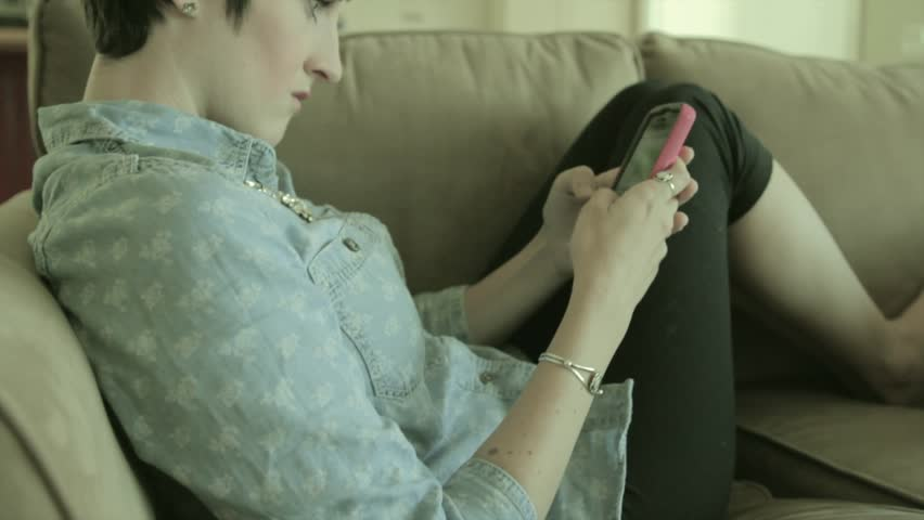 A woman sending a text message from her smart phone while resting on the couch