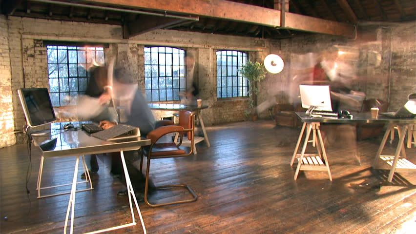 Time lapse of small creative business and team working in casual chic downtown loft office.