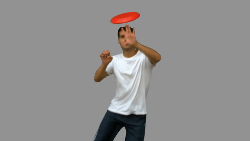 Man jumping and catching a frisbee on grey screen in slow motion - HD stock footage clip