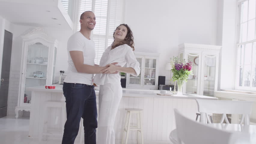 Happy and attractive young mixed race couple viewing a beautiful modern property with a view to making it their home. In slow motion. #4531829