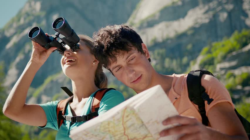 Man and woman during leisure activities on holidays, young people hiking and trekking on mountains, talking, and looking at map with binoculars. Part 3 of 12