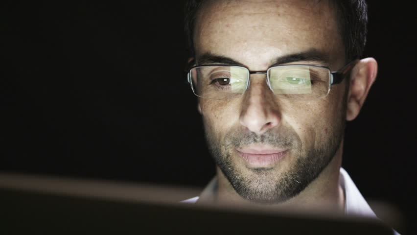 Close up of young man reading his tablet in the dark. Black background.