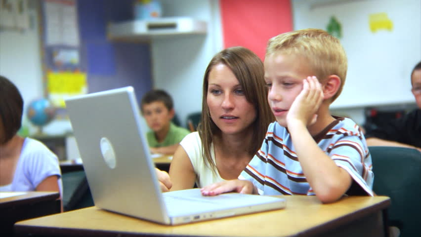 elementary school students looking at laptop computer