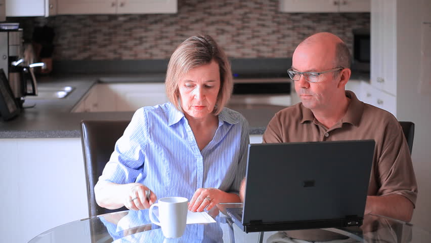 Middle Aged Mature Couple At Home In The Kitchen Using A Laptop Computer To Pay Bills And Prepare Income Tax Returns