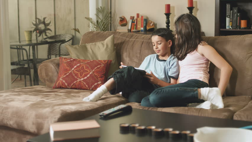Cute siblings play on a tablet computer together on the couch sofa. Wide shot - HD stock video clip
