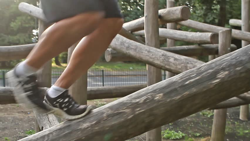 Man jumping across beams of wood for parkour training - HD stock footage clip