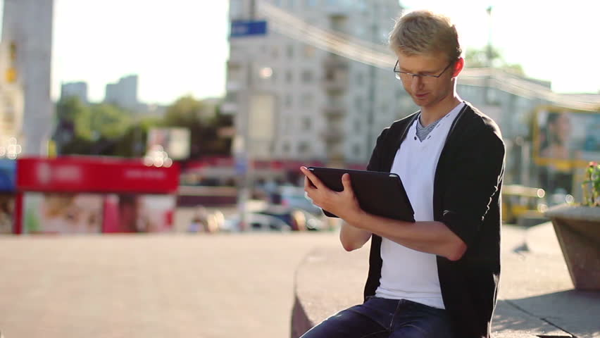Man reading tablet pad writing browsing photos, looking camera