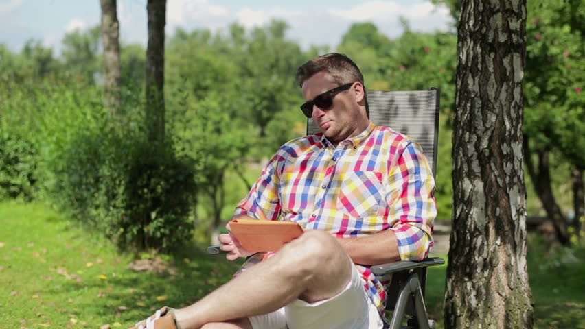Man with tablet relaxing in the garden  - HD stock footage clip