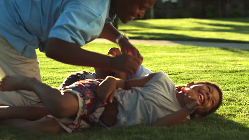 African American dad plays with his sons by tickling them. Medium shot