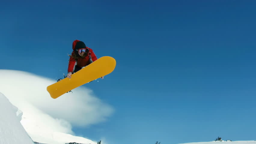 Snowboarder jumps into sky, slow motion