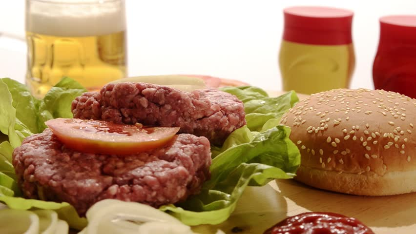 raw burgers, beer, mustard and ketchup