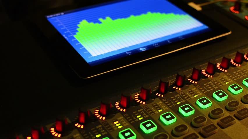 Music studio audio mixer with digital VU meter display showing audio waves.