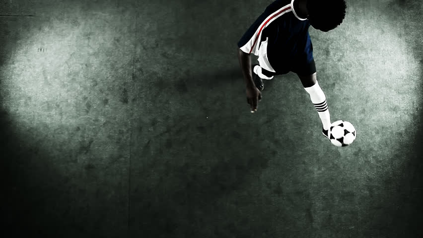 Skillful athlete juggles a soccer ball. Wide shot as seen from a high angle above - HD stock video clip