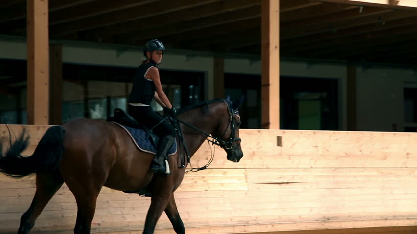 young girl on horse doing circles in big hall - HD stock footage clip
