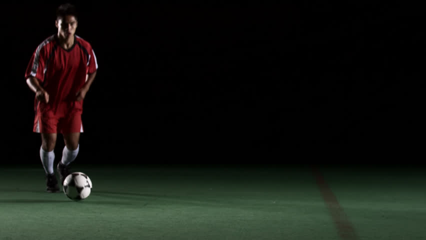 Soccer player follows the ball and kicks it. Medium shot. - HD stock footage clip