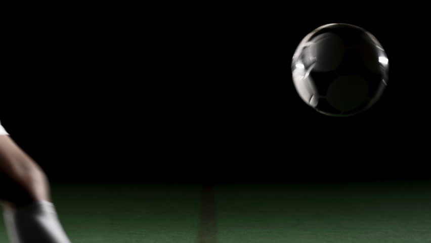 A soccer, or football, player that is dramatically and artistically lit, on an artificial field pitch on a black background, kicks a ball away from the camera at a medium height