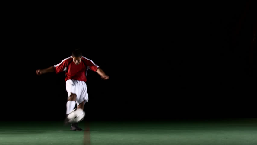 A soccer, or football, player that is dramatically and artistically lit, on an artificial field pitch on a black background, runs up and kicks the ball very hard and fast - HD stock footage clip