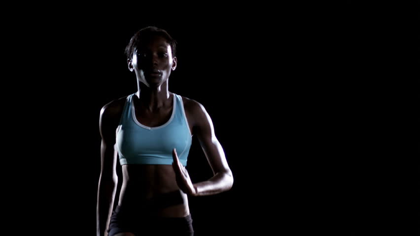 A female athlete runs in place while kicking their legs high in the air in a dark gym - HD stock video clip