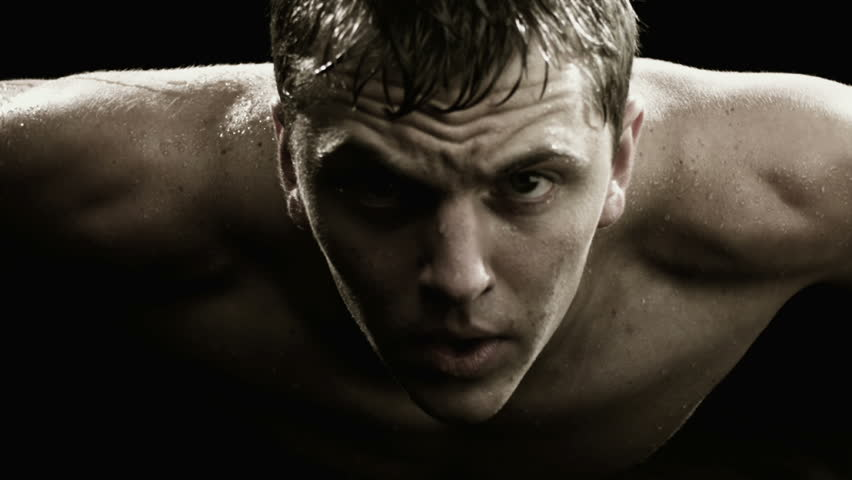 A close up of man doing push ups and sweating