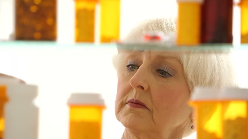 Senior woman looking for pills in medicine cabinet - HD stock video clip