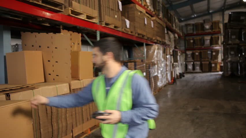 Man in shipping warehouse scans labels on boxes - HD stock footage clip
