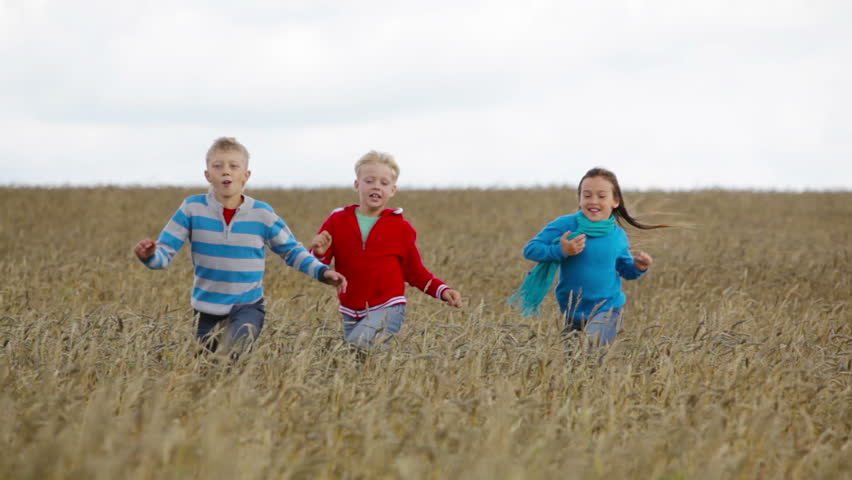 Cute kids running across the field enjoying freedom of being a child - HD stock footage clip