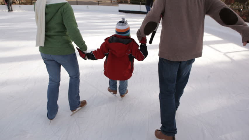 Family holding hands while ice skating - HD stock video clip