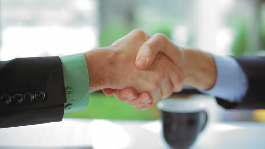 Close up of two businessmen shaking hands to close a deal. Close up shot.
