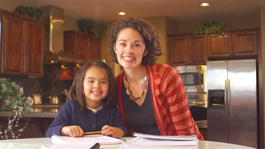 A mother and daughter doing homework in the kitchen look into the camera and smile | Shutterstock HD Video #4637201