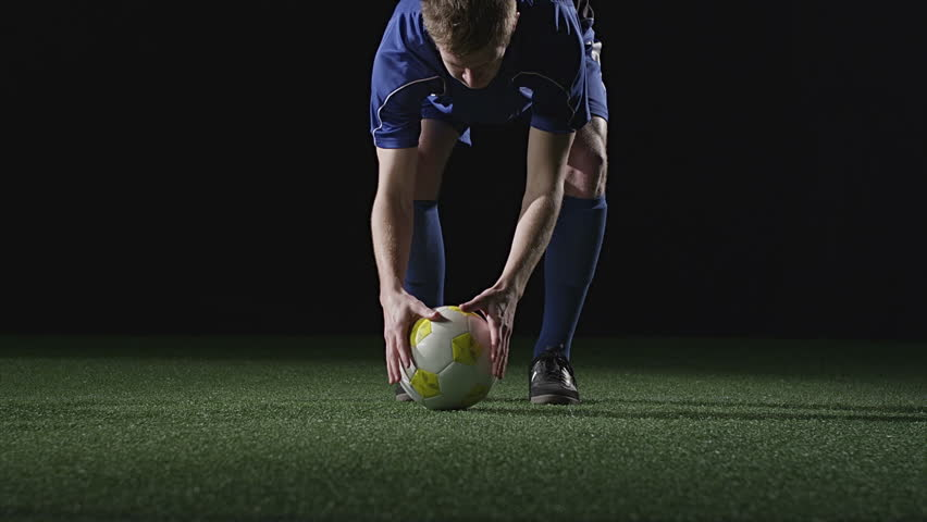 Low angle shot of a soccer player placing a ball and then running up and kicking it