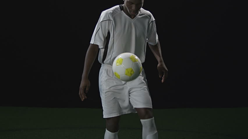A talented soccer player dribbles a soccer ball with his feet before catching it and looking into the camera. Medium slow motion shot. - HD stock video clip
