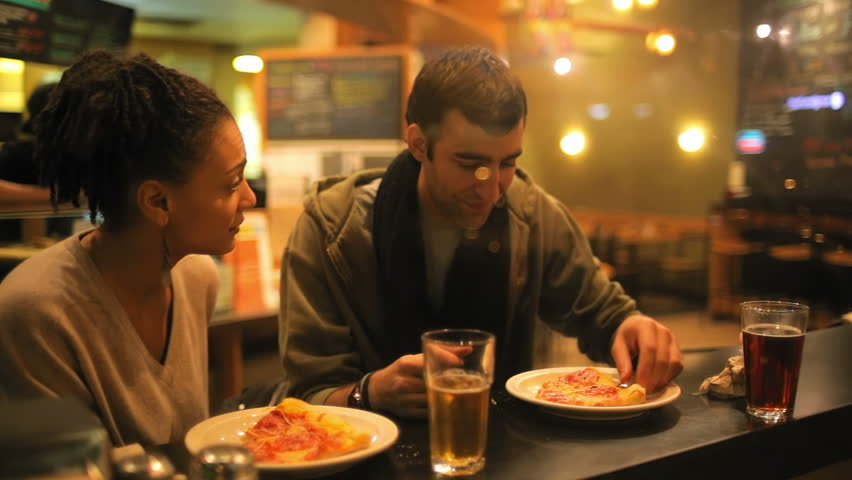 A good looking couple eat some pizza while on a date together. Medium shot. - HD stock footage clip