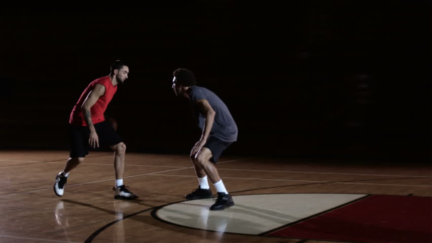 A basketball player dribbles past a defender and then dunks the ball