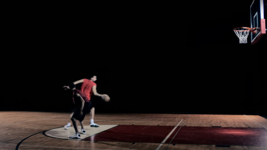 Basketball players playing a game of one on one. The player with the ball spins around his defender and dunks it forcefully.