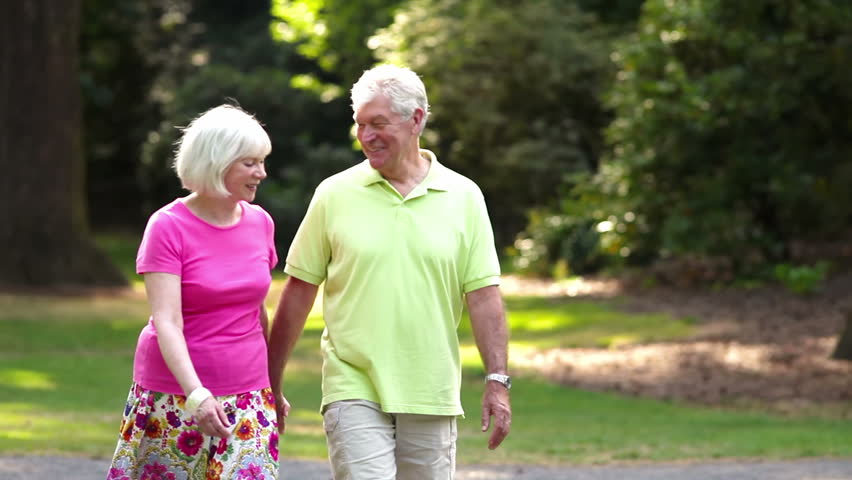 Happy senior couple hold hands and walk together. Medium shot. - HD stock footage clip
