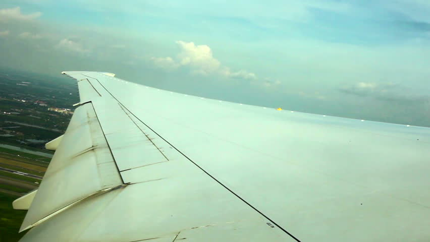 WINDOW VIEW OF WING PLANE OVER GROUND