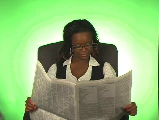 A lovely young businesswoman, sitting in an office chair, reads a newspaper. - SD stock footage clip