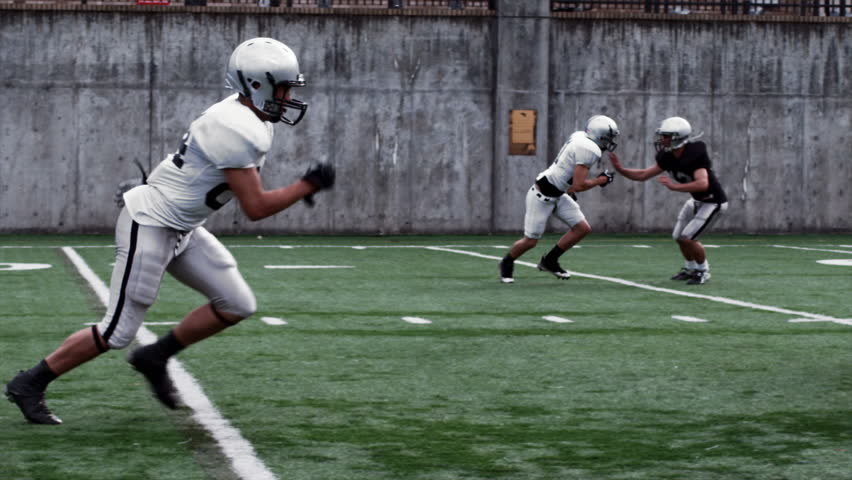 A Running Back receives a handoff and sidesteps and spins passed defenders. Camera dollies with him. - HD stock footage clip