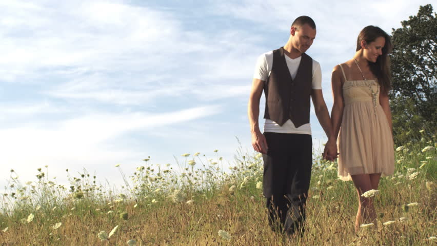 Couple In Field Holding Hands Walk Away From The Camera