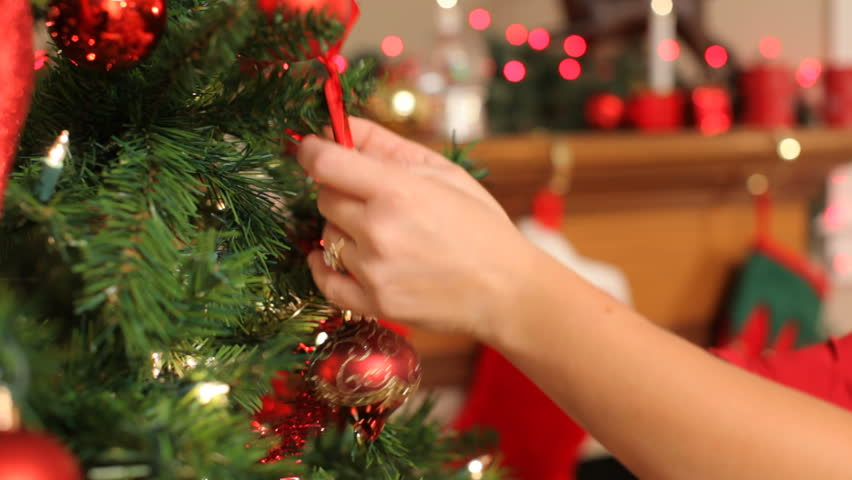 Putting ornament on Christmas tree, closeup