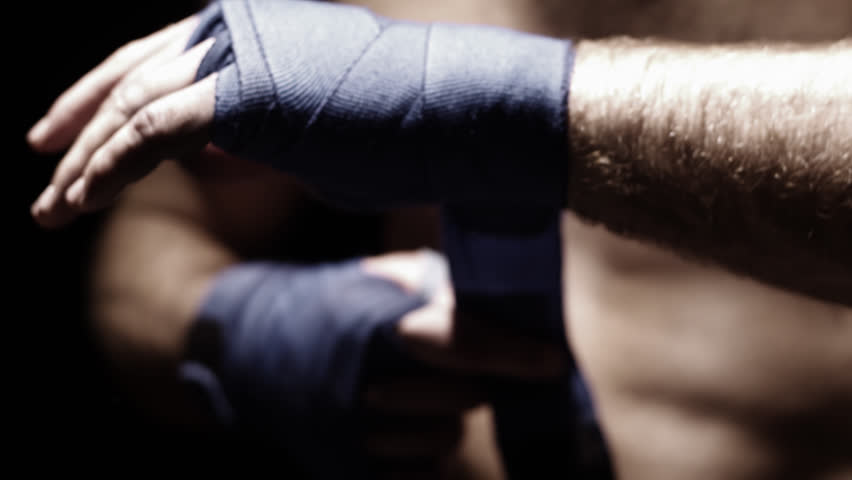 Mixed martial arts athlete wraps his hand with blue cloth. Close up shot. - HD stock footage clip