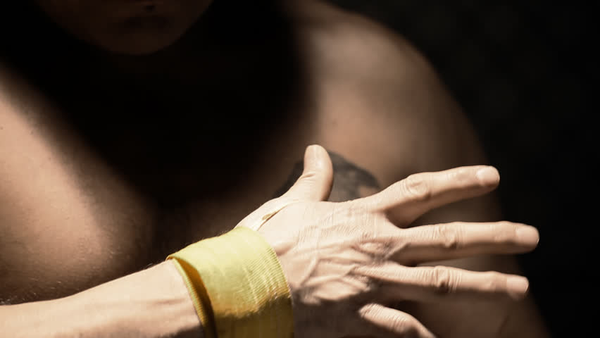 Native American athlete wraps his hand with yellow tape. Close up shot. - HD stock footage clip