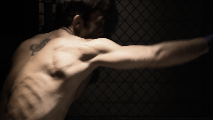 Profile of a mixed martial arts athlete shadow boxing. Medium shot. - HD stock footage clip