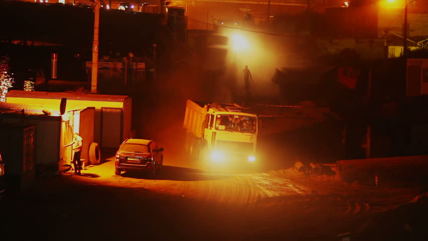 Construction site at night, trucks lorries drive in out, yellow