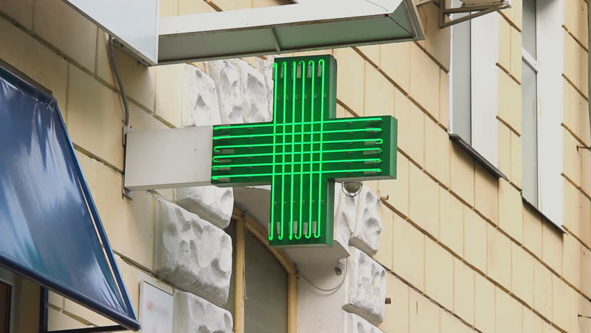 Pharmacy, drug store green neon cross lighted at daytime, city