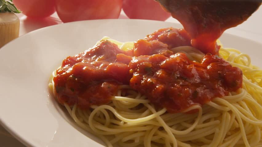 Pouring marinara sauce onto spaghetti