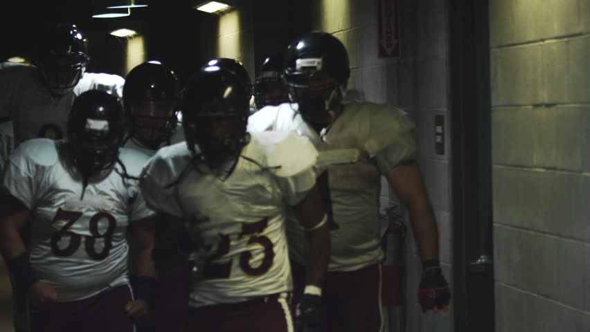 An excited football team walks down a dark tunnel towards the field before a game